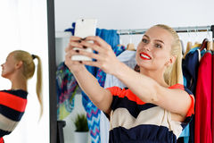 Blonde woman standing near wardrobe rack full of clothes and mir Royalty Free Stock Images