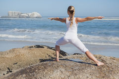 Blonde woman standing in warrior pose on beach on rock Stock Photography