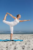Blonde woman standing in warrior pose on beach Royalty Free Stock Photos