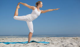 Blonde woman standing in warrior pose on beach Royalty Free Stock Image