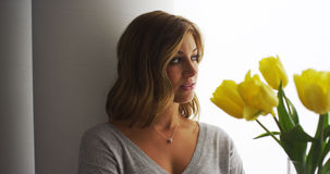 Blonde woman standing by a window with a bouquet of tulips Royalty Free Stock Photos