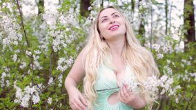 Blonde woman stands among flowering bushes. Young beautiful blonde woman stands among flowering bushes and admires nature stock video