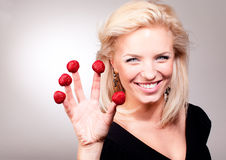 Blonde woman stick strawberry on Stock Images