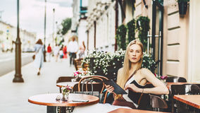 Blonde woman in street bar with digital tablet Royalty Free Stock Images