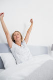 Blonde woman stretching in bed in the morning Stock Photography