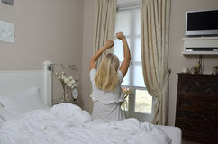Blonde Woman Stretching in Bedchamber Royalty Free Stock Photo