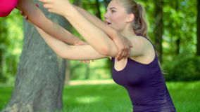 Blonde woman stretching with help of friend outdoor. Sport woman stretching stock video footage