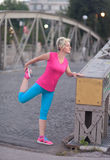 Blonde woman  stretching before morning jogging Royalty Free Stock Photos