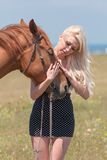Blonde woman stroking gelding Royalty Free Stock Image