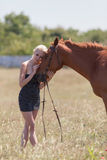 Blonde woman stroking gelding Royalty Free Stock Images
