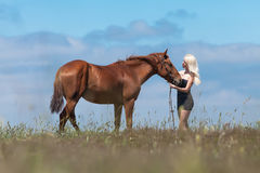 Blonde woman stroking gelding. Young blonde woman in polka-dot dress with brown horse Stock Images