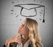 Blonde woman student thinks about her graduation stock photography