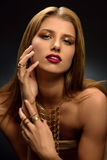 Blonde woman with styled make–up, long necklace and many rings on her fingers Stock Photo