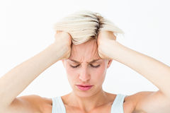 Blonde woman suffering from headache holding her head Royalty Free Stock Photography
