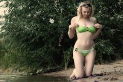 Blonde woman on summer beach. Blonde woman corrects bikini on summer beach Royalty Free Stock Images