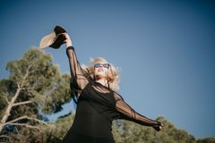 Young blonde woman jumping in nature with black sunglasses and clothes and a hat. Blonde woman with sunglasses and black clothes jumping in the forest with a Stock Images