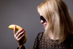 Blonde woman in sunglasses is holding a banana. Isolated on gray background Stock Photo