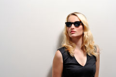 Blonde woman with sunglasses. Long haired blonde woman wearing sunglasses while standing in the sunlight Stock Images