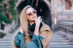 Blonde woman in sunglasses outdoors city walk. Fashion look girl model travel in coat on stairs in autumn Royalty Free Stock Images