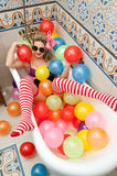 Blonde woman with sunglasses playing in her bath tube with bright colored balloons. Sensual girl with white red striped stockings. Blonde woman with sunglasses stock images