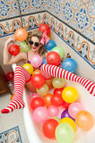 Blonde woman with sunglasses playing in her bath tube with bright colored balloons. Sensual girl with white red striped stockings. Blonde woman with sunglasses royalty free stock images