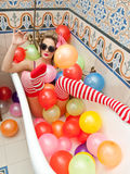 Blonde woman with sunglasses playing in her bath tube with bright colored balloons. Sensual girl with white red striped stockings. Blonde woman with sunglasses royalty free stock image