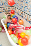 Blonde woman with sunglasses playing in her bath tube with bright colored balloons. Sensual girl with white red striped stockings Royalty Free Stock Image