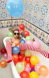 Blonde woman with sunglasses playing in her bath tube with bright colored balloons. Sensual girl with white red striped stockings. Blonde woman with sunglasses stock image