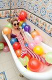 Blonde woman with sunglasses playing in her bath tube with bright colored balloons. Sensual girl with white red striped stockings Royalty Free Stock Images
