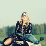Blonde woman in sunglasses on a sports motorcycle Stock Image