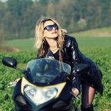 Blonde woman in sunglasses on a sports motorcycle Royalty Free Stock Image
