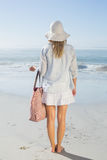 Blonde woman in sunhat carrying beach bag looking out to sea Stock Photos