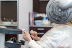 A blonde woman surfing the internet with her smartphone in hair studio Royalty Free Stock Photo