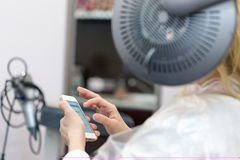 A blonde woman surfing the internet with her smartphone in hair studio. A blonde woman surfing the internet with her smartphone while having her hair coloring Royalty Free Stock Photo