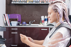 A blonde woman surfing the net with her smartphone during hair colouring. A blonde woman surfing in the net with her smartphone during hair colouring Stock Photography