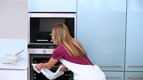 Blonde woman taking cookies in oven in kitchen Stock Image