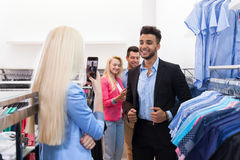 Blonde Woman Taking Photo Of Young People Shopping, Happy Smiling Friends Customers In Fashion Shop Royalty Free Stock Photography