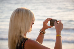 Blonde woman taking picture on mobile phone Royalty Free Stock Photos