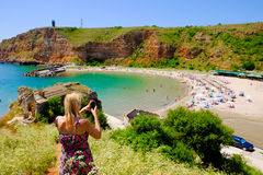 Blonde woman taking pictures at Bolata bay, Bulgaria, Black Sea. Royalty Free Stock Images