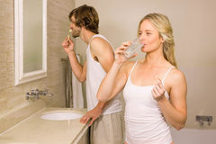 Blonde woman taking a pill with her boyfriend brushing his teeth Royalty Free Stock Photography