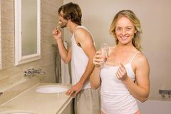 Blonde woman taking a pill with her boyfriend brushing his teeth Stock Photography