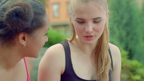 Blonde woman talking with african girlfriend outdoor. Multiracial friends. Closeup girls talking. Attractive women talking in park. Multicultural friends stock video footage