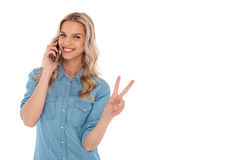 Blonde woman talking on  phone and making the victory sign Stock Photo