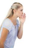 Blonde woman telling a secret Royalty Free Stock Image