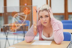 Blonde woman thinking hard while studying on interface with DNA Royalty Free Stock Image