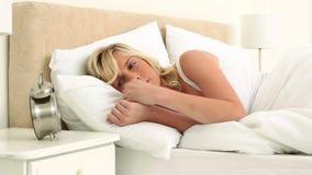 Blonde woman throwing her alarm clock away stock footage