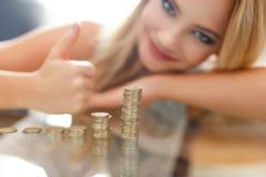 Blonde woman thumb up at growing euro columns Stock Photos