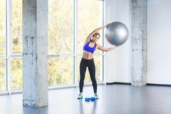 Blonde woman tilt side, holding fit ball. royalty free stock image