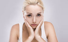 Blonde woman with toothache. Portrait of a caucasian blonde woman with toothache on grey background Royalty Free Stock Images