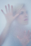 Blonde woman touching frosted glass Stock Images